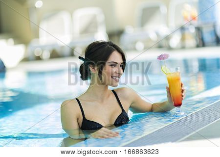 Beautiful lady drinking a cocktail in a swimming pool and relaxing