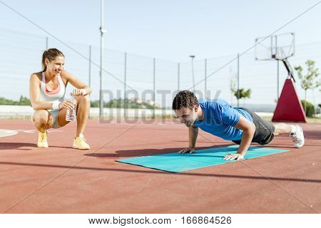 Young, Beautiful, Fit And Healthy Personal Trainer Counting Push-ups