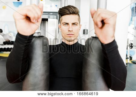 Portrait of a handsome young man training in a gym and looking towards the camera