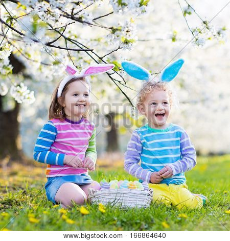 Kids on Easter egg hunt in blooming spring garden. Children with bunny ears searching for colorful eggs in apple blossom orchard. Toddler boy and preschooler girl in rabbit costume play outdoors.