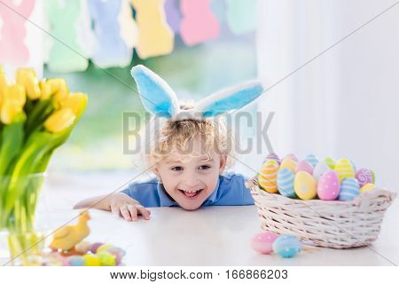 Funny little boy in bunny ears at breakfast on Easter morning at table with Easter eggs basket. Kids celebrating Easter. Children on Easter egg hunt. Home decoration - pastel bunny banner and flowers.