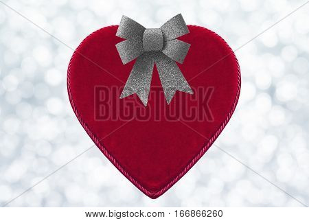 Red heart-shaped velvet box for Valentine's day gift isolated on bokeh background with silver shiny glitter bow