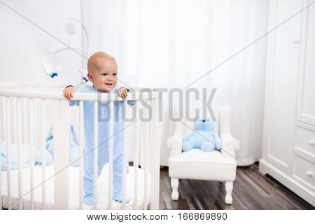 Baby Boy Standing In Bed In White Nursery