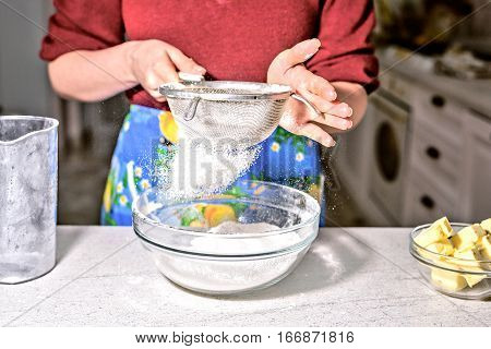 Woman sifting flour through sieve. Baking ingredients. Home cooking