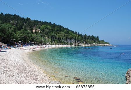 PAXOS, GREECE - JUNE 14, 2014: The popular Manadendri beach between Lakka and Loggos on the Greek island of Paxos. The 13km long Ionian island has a population of around 2300 people.