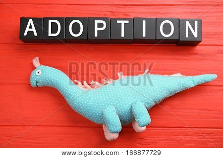 Black cubes with word ADOPTION and dinosaur toy on color wooden background