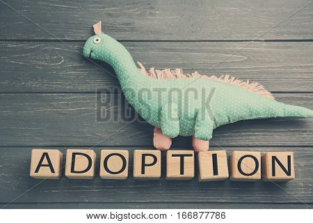 Cubes with word ADOPTION and dinosaur toy on wooden background