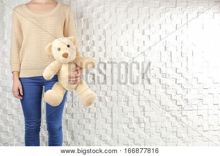 Child custody concept. Closeup of girl with teddy bear on white textured background