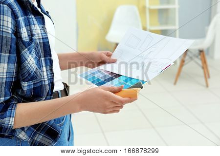 Young female decorator choosing colors for new flat, closeup