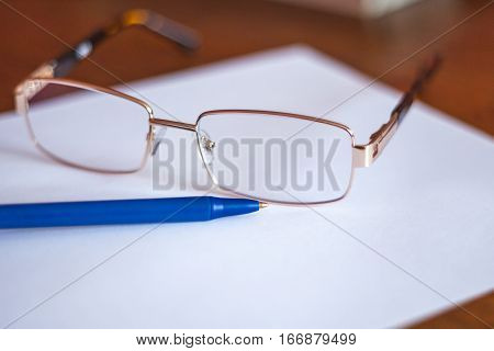 Ballpoint Pen On A Sheet And Reading Glasses