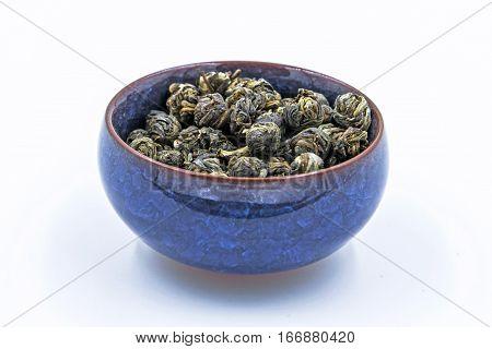 Chinese green tea Jasmine Pearl (Mo Li Long Zhu) in a blue ceramic bowl isolated on white.