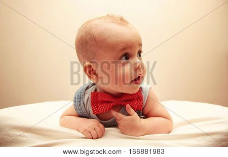 Child With Bowtie Lying On The Bed