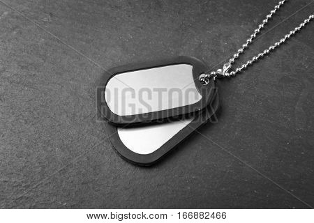 Military ID tags on dark background