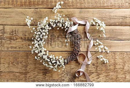 Beautiful floral wreath with satin ribbon on wooden background