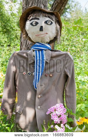 garden scarecrow to stand among green bushes