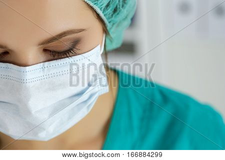 Close up portrait of female medical doctor or nurse wearing protective cap and mask looking down. Surgery medical assistance hospital epidemic and healthcare concept.