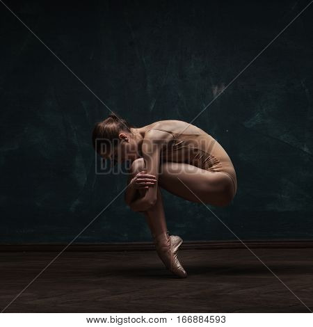 young beautiful ballet dancer in beige swimsuit posing on pointes over dark grunge background