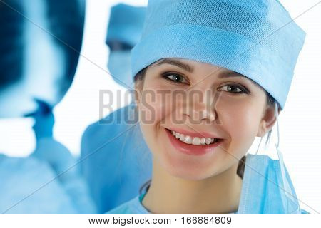 Close up portrait of young smiling female surgeon doctor surrounded by her team. Group of surgeon in operation theatre. Healthcare medical education emergency medical service and surgery concept