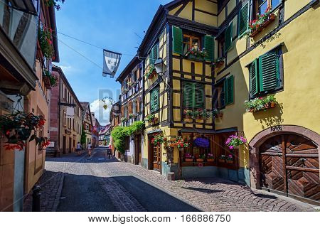 View along the streets of the old French town. Along the street arranged colorful half-timbered houses. In the distance can be seen the figure of tourists.Ribeauville, Alsace.