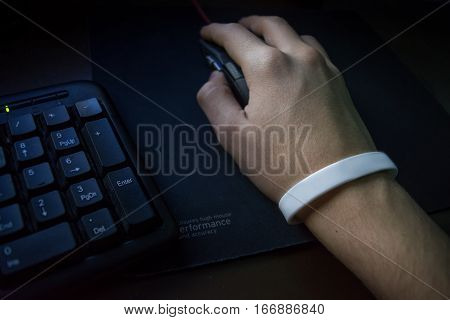 Male hand with bracelet holding computer mouse