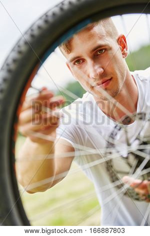 Man fixing wheel of bike in summer in nature