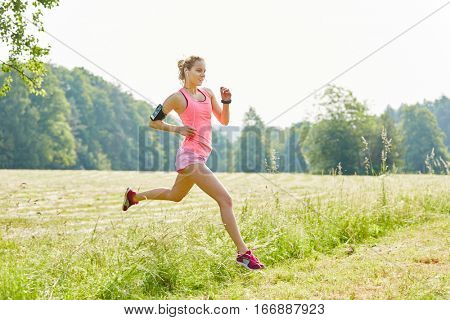 Young woman with smartwatch as jogger running fast in the park
