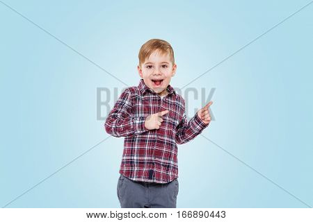 Surprised little boy standing and pointing finger away isolated over blue background