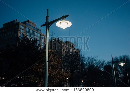 Lighted lantern on a dark blue sky with buildings on the background
