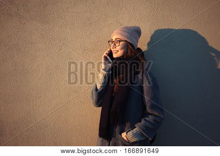 Portrait of a smiling young woman in hat and eyeglasses talking on mobile phone and looking away isolated