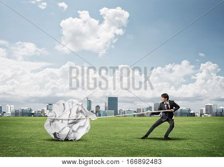 Young businessman outdoors making huge paper ball move