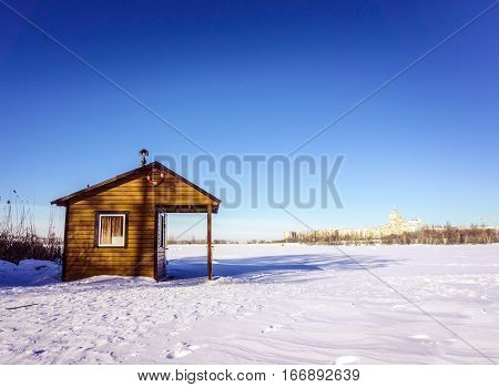 Wooden house rescuers on the shore of a frozen lake covered with snow in Voronezh. Sunny winter day with clear skies