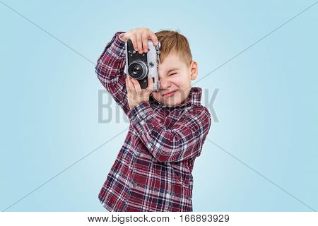 Portrait of a little boy in shirt taking picture with vintage retro camera over blue background
