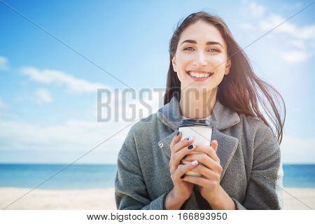 Close-up portrait of a smiling cheerful girl holding takeaway cup at the seaside