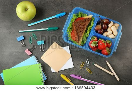Tasty sandwich and fruits in lunchbox and stationery on dark background