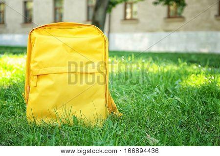 Yellow rucksack on green grass