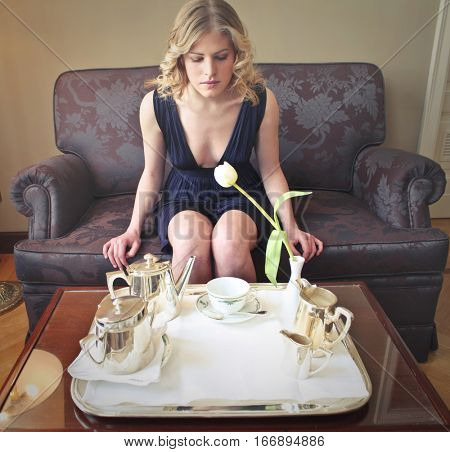 Blonde girl in beautiful black dress having breakfast on fancy sofa