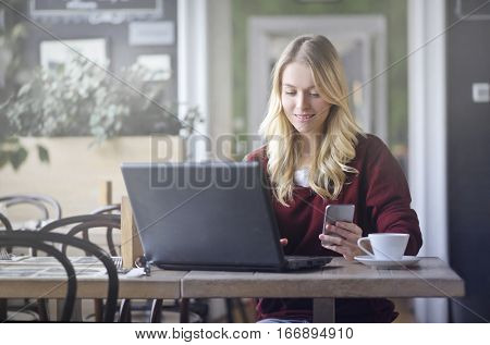 Blonde working on her laptop and phone simultanously while in a bar