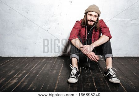 Photo of handsome young bearded hipster man wearing hat dressed in shirt in a cage sitting on floor isolated over wall background while listening music with earphones.