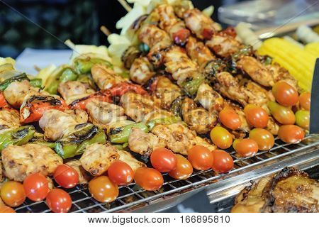 Chicken tomato and hot peppers on skewers are being grilled by a street vendor in Thai street night market. Deep fried snacks fresh and hot Thai food.