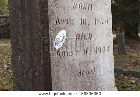 Grave marker that has a sticker that says I voted