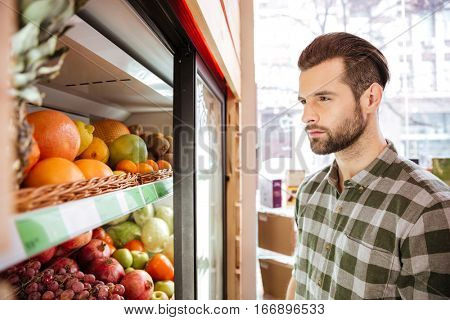 Handsome bearded young man standing and choosing fruits in grocery shop