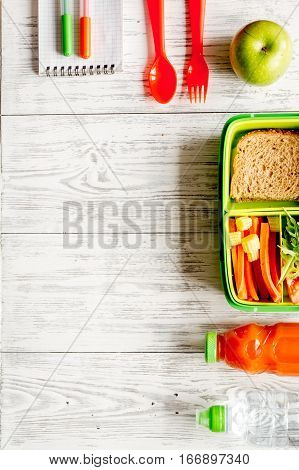 kid menu lunchbox for school with vegetables and fruit to school top view on wooden background