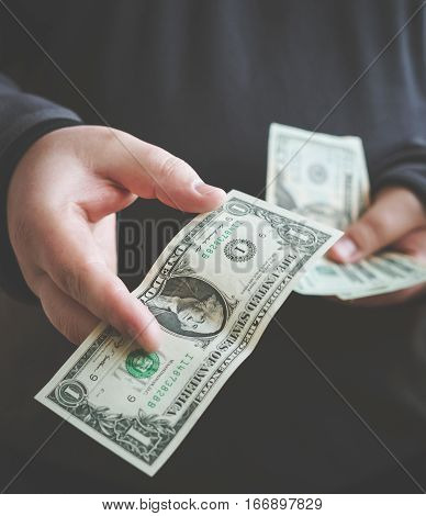 Man giving money one us dollar banknote and holding cash in hands. Money credit concept. Vertical image. Toned picture.