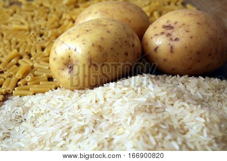 Rice, Potatoes And Macaroni Pasta On A Wooden Table.three Common Carbohydrates Which Provide Energy