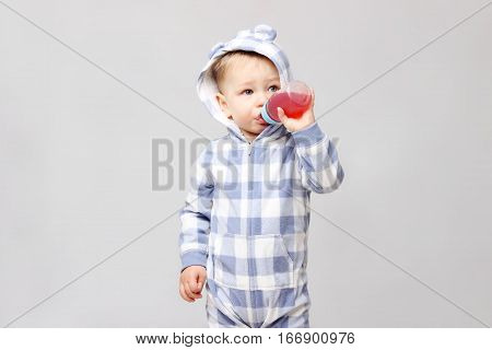 Shot of a little baby boy drinking from a sippy cup.