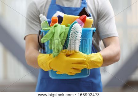 Young man holding bucket with cleaning equipment and supplies indoors, closeup