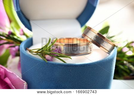 Box with wedding rings and flowers, closeup
