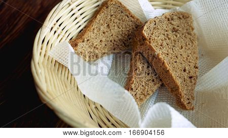 Close-up of basket with three pieces of bread in it on restaurant wooden table. Remains of lunch. Detailed shot.