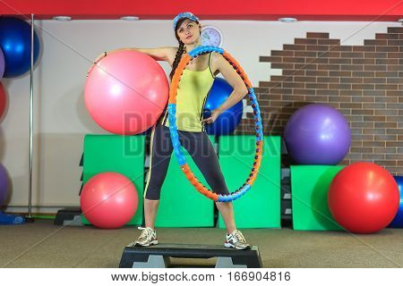 Young Beautiful White Girl In A Yellow And Gray Sports Suit Stands With A Fit Ball, Hoop And A Dumbb
