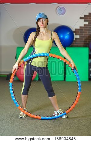 Young Beautiful White Girl In A Yellow And Gray Sports Suit Stands With A Hoop At The Fitness Center